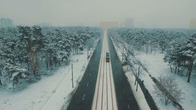 Above top view on winter forest road with cars and tram. Snowfall aerial drone footage. 4K UHD stock footage