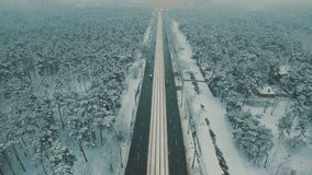 Above top view on winter forest road with cars and tram. Snowfall aerial drone footage. 4K UHD stock video footage