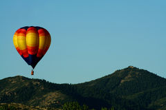 Above the tree tops. A colorful hot air balloons floats above the hills Royalty Free Stock Photography