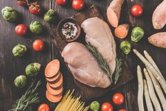 Raw chicken breasts and vegetables. From above uncooked chicken breasts and fresh vegetables on wooden table Royalty Free Stock Image