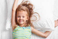Above view of attractive light haired small child, has blue eyes, stretches in bed, lies on white pillow, dressed in colourful str. Iped pyjamas, enjoys royalty free stock photo