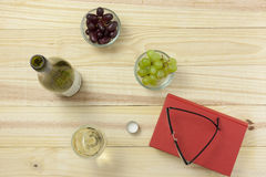 Above view of a book on a wooden table with reading glasses. Wine bottle and a glass of wine and bowls of grapes stock photo