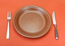 Above view of ceramic plate, fork, knife on red Stock Photos