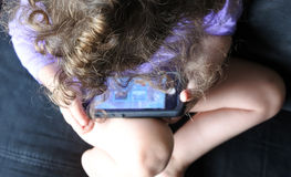 Above view of a child plays on mobile phone Royalty Free Stock Photo