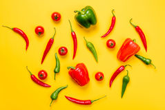 Above view at Chili pepper and Capsicum. With tomatoes on yellow background stock photo