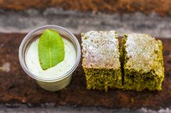 Above view of a coca yogurt served in a plastic glass with a mint leaf inside and a delicious cake over a brick in a. Blurred background Stock Photos