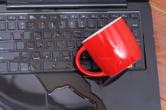 Above view of coffe drop and a red cup of coffe over the laptop, damage liquid wet and spill on keyboard, accident. Concept Royalty Free Stock Photos