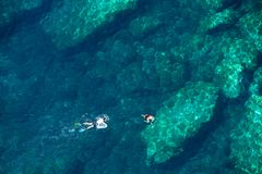 Above view of a couple snorkeling in tropical sea water. Drone view of a couple snorkeling in tropical sea water Royalty Free Stock Photography