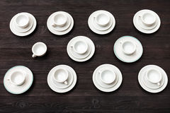 Above view of cups and saucers on dark brown board Stock Photos
