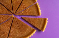 Sliced pumpkin pie close-up and one piece separated. Top view stock photos