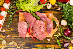 Above view on cuts of meat with peppers Royalty Free Stock Photography