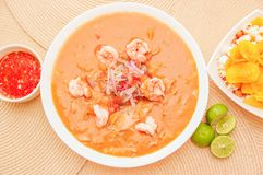 Above view of Ecuadorian food: shrimp cebiche with some chifles inside white bowl, lemon and red spicy salad inside a. White bowl in a wooden table background Royalty Free Stock Photography