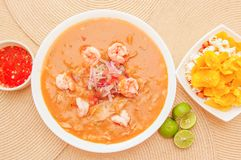 Above view of Ecuadorian food: shrimp cebiche with some chifles inside white bowl, lemon and red spicy salad inside a. White bowl in a wooden table background Royalty Free Stock Image