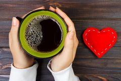 Above view of female hand holding hot cup of coffee with red heart on wood table. Photo in vintage color image style.  stock photo