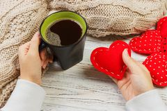 Above view of female hand holding hot cup of coffee with red heart on wood table. Photo in vintage color image style.  stock images