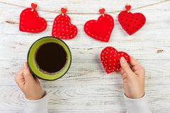 Above view of female hand holding hot cup of coffee with red heart on wood table. Photo in vintage color image style.  royalty free stock photo