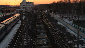 Above view of freight train with flatcars passing by railway station at sunset. Above view of cargo train with flatcars passing by railway station at sunset stock video