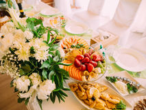 The above view of the fruit and different dishes placed on the wedding table near ther huge white bouquet. Royalty Free Stock Image