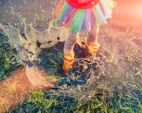 Crop girl playing in muddy puddle Stock Image