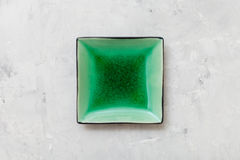 Above view of green square saucer on gray concrete. Board Stock Image