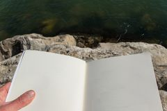 Above view of the hand of an adult person holding open book. Sitting on the sea rocks Stock Image