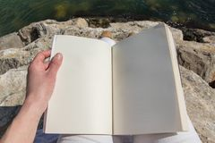 Above view of the hand of an adult person holding open book. Sitting on the sea rocks Royalty Free Stock Photography