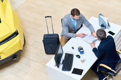Businessman Signing Car Lease Agreement. Above view of handsome men reading lease contract sitting at desk in dealership shop before renting luxury car for Stock Image