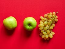 Isolated set of a green apple with a bunch of sweet seedless grapes in studio with red background. Above view of isolated set of a green apple with a bunch of royalty free stock photo
