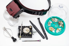 Above view of kit of tools with head-mounted lens. Watchmaker workshop - above view of kit of tools with head-mounted magnifier and spare parts for repairing Royalty Free Stock Images