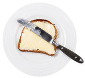 Above view of knife on bread and butter on plate Royalty Free Stock Images