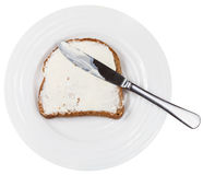 Above view of knife on bread with spread on plate Royalty Free Stock Photography