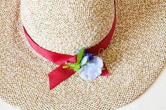 Above view of ladies` wide brim straw hat. With red band and textile flower Stock Photos