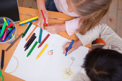 Above view of little schoolgirls drawing. In a classroom Stock Image