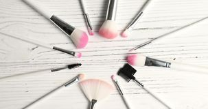 Brushes for makeup in circle. From above view of makeup brushes of different kind laid in circle on wooden background stock video