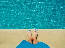 Above view on male foots near pool. Summertime vacation Royalty Free Stock Photos