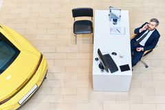 Car Salesman Speaking by Phone. Above view of mature salesman sitting at desk speaking by phone in empty showroom selling luxury cars, copy space royalty free stock photography