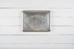 Above View of a Metal Cookie Sheet Cooking Pan Laying or Hung in center of a Rustic White or Gray Wood Board Background blank area Royalty Free Stock Photography