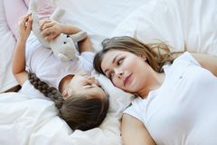 Mother and Daughter Lying on Bed stock photos