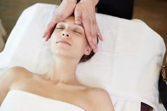 Woman Enjoying Face Lifting Massage in SPA. Above view portrait of young women enjoying face lifting massage lying with eyes closed in SPA center and relaxing stock image