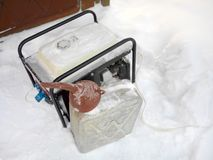 Jerrycan And Power Generator. Above view of a power generator, jerrycan and funnel on the snow Stock Image