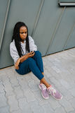 The above view of the sad afro-american teenager sitting on the ground and leaning on the wall. She is texting via the Stock Photography
