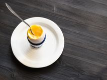 Soft-boiled egg with spoon in cup on plate on dark stock photography