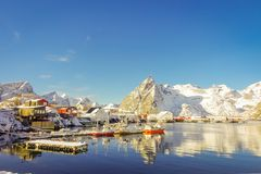 Above view of some wooden buildings in the bay with boats in the shore in Lofoten Islands surrounded with snowy. Mountains and colorful winter season, in Norway Stock Photo
