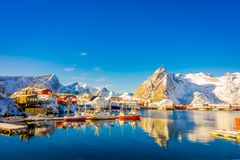 Above view of some wooden buildings in the bay with boats in the shore in Lofoten Islands surrounded with snowy. Mountains and colorful winter season, in Norway Stock Images