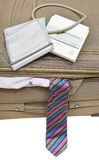 Above view of sphygmometer on suitcase with tie. Above view of sphygmometer on suitcase with male tie isolated on white background Royalty Free Stock Photos