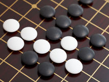 Above view of stones during go game playing. On wooden goban Stock Photography