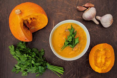 Above view on table with bowl of pumpkin soup with parsley Stock Photos