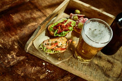 Above view on tapas shrimp and vegetable snack with beer Stock Photo