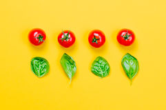 Above view at tomatoes and basil. On yellow background Stock Images