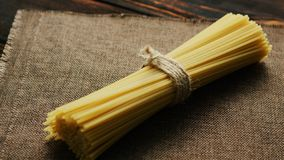 Bunch of raw spaghetti. From above view of uncooked spaghetti tied with rope and placed on textile napkin royalty free stock photography